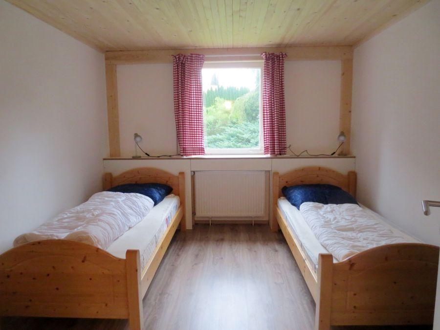 Schlafzimmer 1 EG:Zwei Einzelbetten, die bei Bedarf zusammengeschoben werden können; Schrank und Sessel (nicht sichtbar).