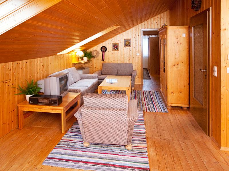 Wohnzimmer Dachgeschoss:Das Wohnzimmer unterm Dach strahlt durch das viele Holz in der Einrichtung eine herrliche Atmosphäre aus! Ebenfalls mit einem Fernseher ausgestattet kann man sich hier einen schönen Abend machen.