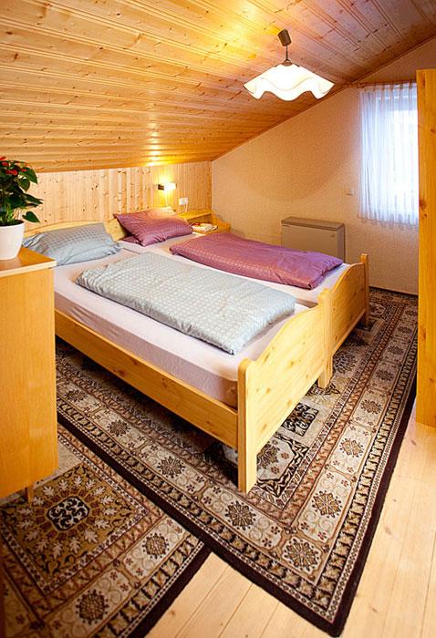 Schlafzimmer 1 DG:Das erste Schlafzimmer im Dach bietet dank der vielen Schränke und Kommoden genügend Stauraum. Die Betten in dem warm eingerichteten Raum versprechen eine angenehme Nachtruhe.