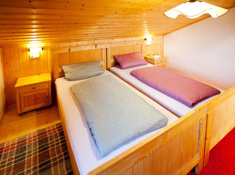 Schlafzimmer 2 DG:Das zweite Schlafzimmer im Dachgeschoss lädt mit seinem Bett im alpenländischen Stil geradezu ein, die Nacht hier zu verbringen und am Morgen mit Blick auf den Grünten aus dem Fenster aufzuwachen!