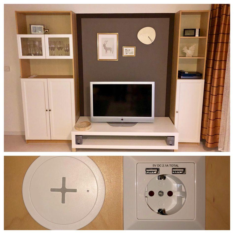 Medienwand:Die Medienwand ist zusätzlich mit USB Ladeanschlüsse und QI Zertifiziertem Ladegerät ausgestattet