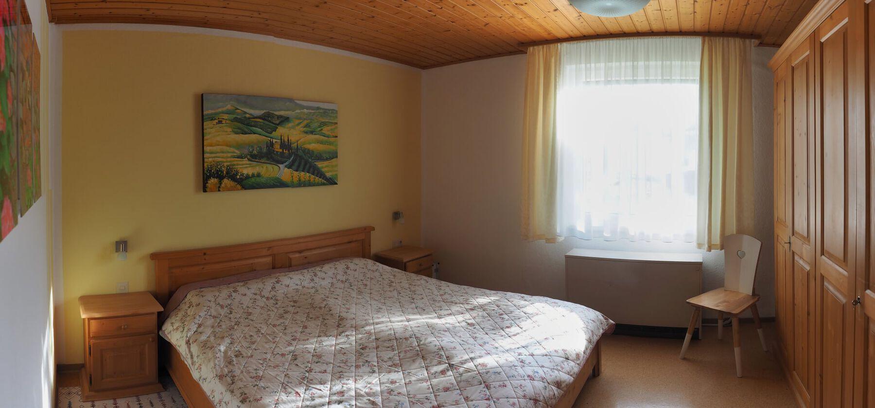 :Schlafzimmer mit Doppelbett und geräumigem Kleiderschrank.